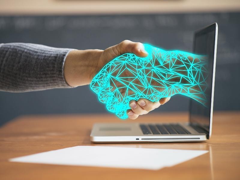 Image of human hand shaking a digital/computer hand